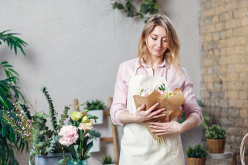 Photo of florist woman in apron with bouquet with kraft paper