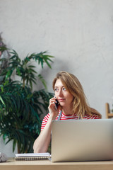 Picture of blonde florist talking on phone sitting at table with computer
