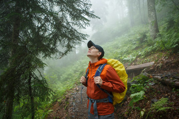 Photo of young man with backpack looking up