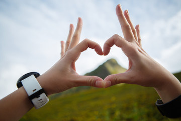 Image of heart from palms against background of mountains