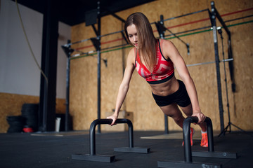 Picture of young woman doing horizontal push-ups with bars
