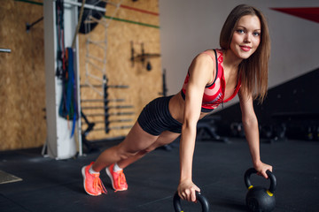 Picture of spotswoman doing horizontal push-ups with kettlebells .
