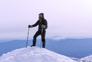 climber in a windproof mask and glasses reached the snow top of the mountain