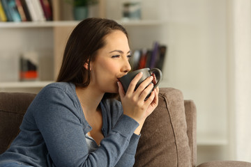 Relaxed happy woman drinking coffee at home