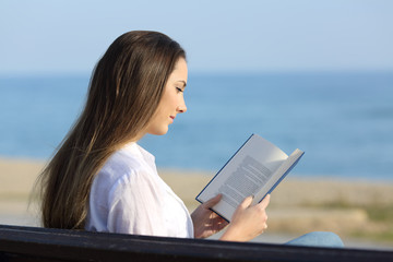 Woman reading a book on a bench on the beach