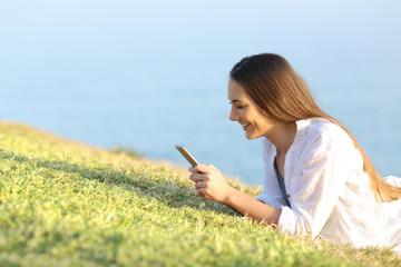 Woman writing text in a smartphone on the grass