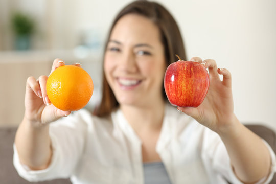 Woman showing two different fruits