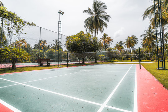 Wide-angle side view of the badminton court located in luxury resort in the Maldives: red and green marked field, palms around, lighting masts, red flower, lanterns and plants; warm sunny day