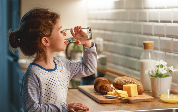 child girl is drinking water in  kitchen at home