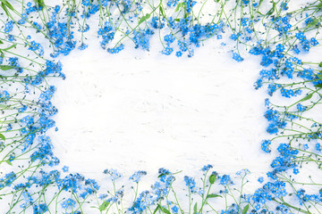 Gentle Frame of blue forget-me-not flowers on white background