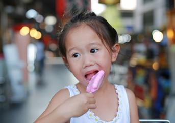 Child girl eating ice-cream in avenue.
