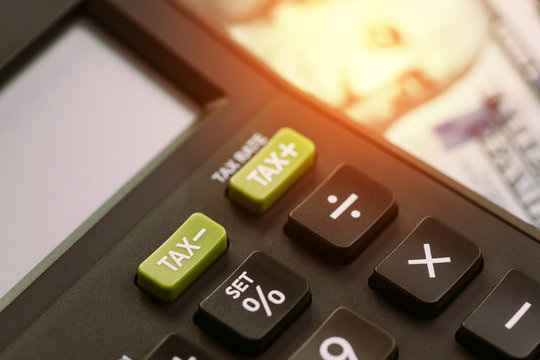 Tax cuts or reduce concept, selective focus on TAX minus buttons on calculator with background of blurred US Dollar banknotes, United States government tax overhaul policy