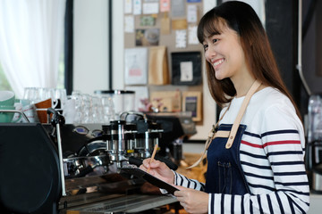 Young asian barista taking note, order, at coffee cafe counter with smiling face, food and drink business concept