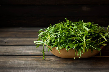 Fresh rucola with water droplets on a dark rustic background