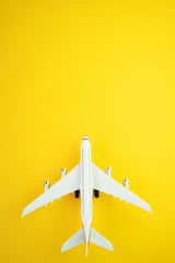 Flat lay design of travel concept with plane  on yellow background with copy space.