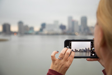 Woman Taking Pictures of The New Orleans Skyline with Her Smart Phone