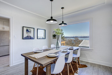 Dining room with white walls and wooden table.