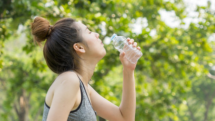 Asian cute sport healthy fit and firm slim teen girl drink water from plastic bottle on the hand in summer hot day at outdoor garden