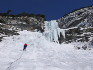 male mountain climber rapelling off a steep and long frozen waterfall in the Swiss Alps in deep winter