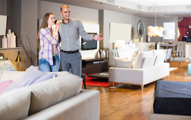Family couple visiting salon of furniture in search of new couch