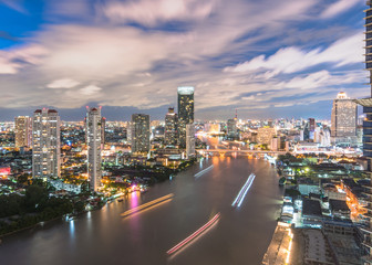 Cityscape night aerial view from rooftop bar over Bangkok's Chao Phraya river CBD and hotel business district after sunset with tourist party sightseeing boat on water travel transportation mode