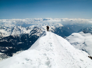 male back country ski mountaineer hiking along a narrow and exposed summit ridge of a high alpine peak