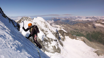 male mountain climber on a high alpine glacier with a great view of the fantastic mountain landscape behind him