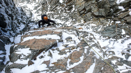 male mountain climber in a steep rock and ice couloir on his way to a high alpine summit