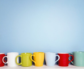 Colorful mugs on a blue background with copy space.
