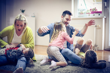 Parents playing with daughters.