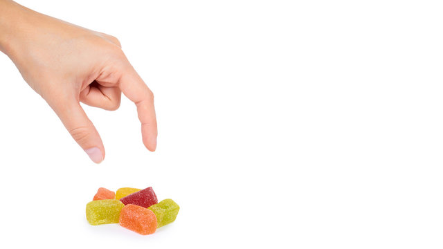 Various color of fruity gummy jelly candies in hand isolated on white background. copy space, template
