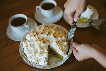 Woman cutting a slice of baked lemon pie in the kitchen