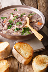 Delicious dietary soup made from wild rice with chicken and vegetables close-up. Vertical