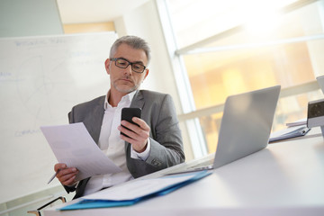 Businessman in office reading message on smartphone