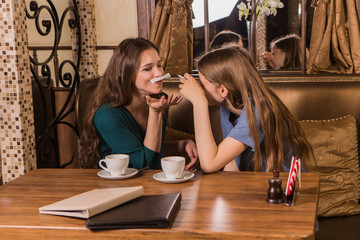 Two happy women plaing with sugar in cafe