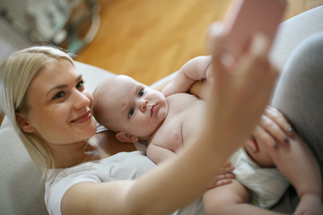 Mother taking self portrait of her and her baby boy at home.