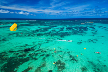 Aerial drone view of people enjoying water sports sea activities for sport, fun, leisure or recreational pursuit near Punta Cana beach. Caribbean sea.