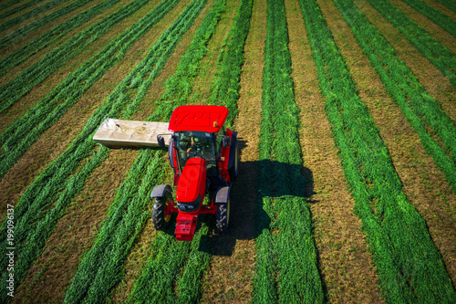 Wall mural Tractor mowing green field, aerial drone view. Farming. Agriculture.