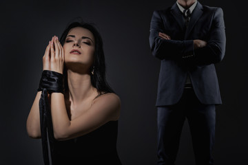 Beautiful woman with tied hands and man in suit on a dark background