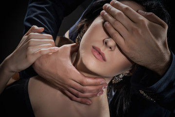 Man covers eyes and stifles woman on black background. Concept of violence, slavery, cruelty