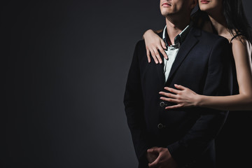 Elegant couple on dark grey background in studio. No face