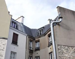 Façade ancienne avec gros tuyau de cheminée en acier brillant.