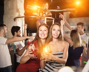 smiling women dancing in the night club with drinks in the hand