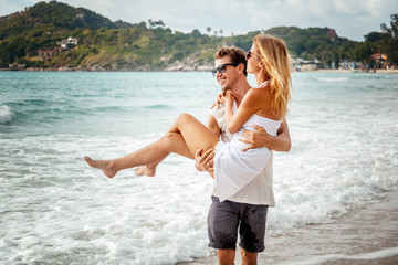 beautiful young couple on the shore of the tropical sea, a man is holding a girl in his arms