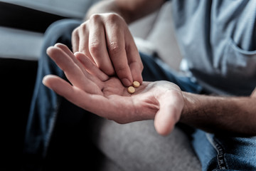 Doctors prescription. Close up of two pills being in hands of a sad cheerless man while suffering from depression