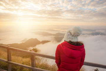 Asian women standing and waiting to see the beautiful sunrise over the sea of mist at Phu Chi Dao mountain in Chiang Rai province of Thailand.