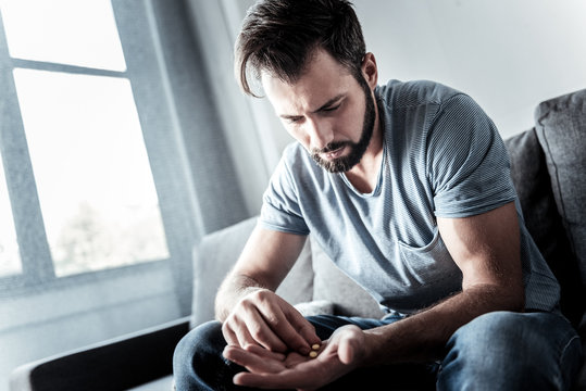 My daily dose. Sad depressed moody man sitting on the sofa and looking at the pills while being ready to take them