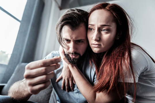We will cope with it. Unhappy depressed young woman sitting together with her boyfriend and hugging him while expressing her love