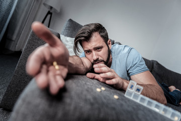 Sudden fatigue. Depressed cheerless unhappy man lying on the sofa and looking at his hand with pills while feeling fatigue
