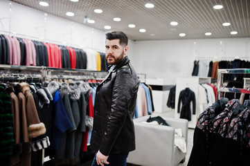 Stylish turkish man at the store of fur coats and leather jackets. Successful arabian beard man.